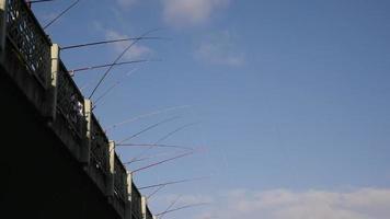 La gente está pescando con cañas de pescar en el puente de Galata, Estambul