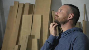 Perfil de hombre peinándose la barba con tablones en el fondo