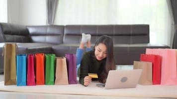 mulher fazendo compras online em casa com sacolas de compras
