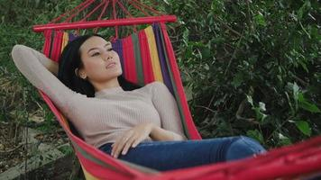 Beautiful young woman lying down to hammock sleeping and relax video