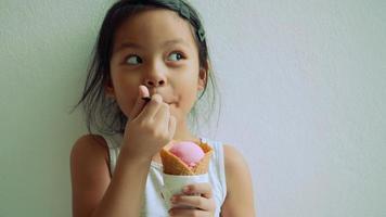 petite fille debout mangeant de la glace et montrant un visage très heureux