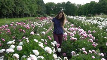 jonge vrouw lopen in een veld van pioenrozen