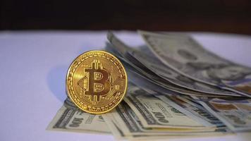 bitcoin dorado con billetes de un dólar