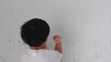 heureux petit garçon écrit sur le mur