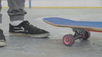 Nahaufnahme eines Mannes, der sein Skateboard aufhebt und es dann fallen lässt