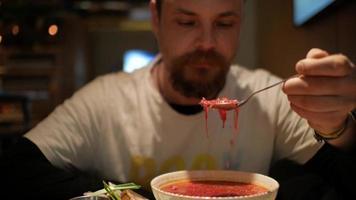 um homem comendo borsch