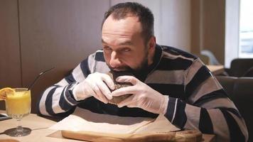 um homem barbudo comendo um hambúrguer