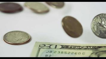 Eine Menge Münzen von einem Viertel Dollar fallen und drehen sich über drei Münzen und eine 20-Dollar-Rechnung auf einem weißen Tisch, schließlich vier Münzen und die Rechnung, die in 4k in die Szene gelegt wurde