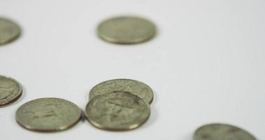 muitas moedas de um quarto de dólar caindo sobre quatro moedas na mesa branca, sete moedas colocadas na cena em 4k