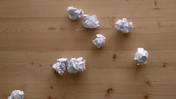 Wirf zerknittertes weißes Papier auf den Holztisch.