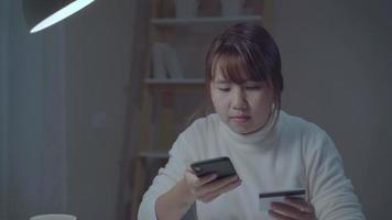 linda mulher asiática usando um smartphone, compras online com cartão de crédito.