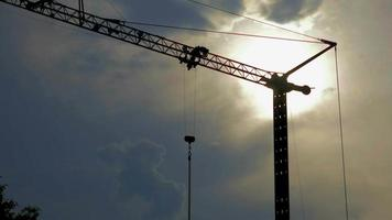 silhouette d'une grue de construction au coucher du soleil 4k vidéo stock