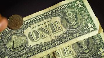 billets d'un dollar et six pièces sur fond sombre