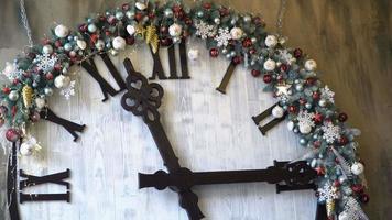 grande relógio branco com mostrador romano com setas decoradas para o natal e brinquedos no estúdio video