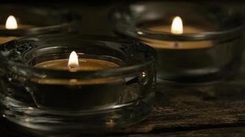 Velas de té con mechas en llamas sobre un fondo de madera - Velas 026