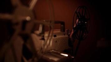 clipe de projetor de filme 8mm chegando na escuridão com foco no rolo de filme no fundo em 4k