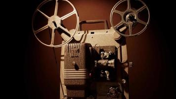 clipe de vista lateral de uma pessoa ligando um projetor de filme com bobinas e mecanismo movendo o filme em 4k