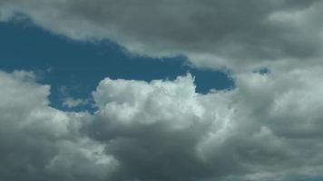 nubes de lluvia que se extienden lentamente por debajo del cielo azul