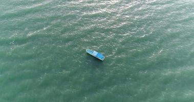 vista superior de un barco azul navegando en el mar