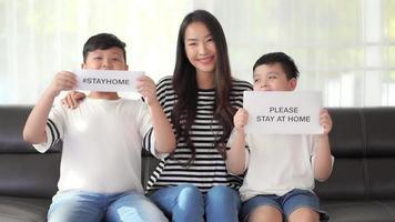 mulher e seus filhos mostram um sinal para ficar em casa video