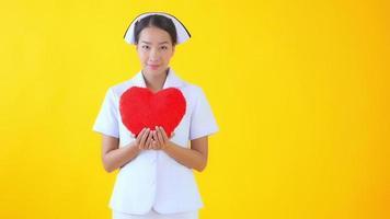 enfermera tailandesa con almohada de corazón