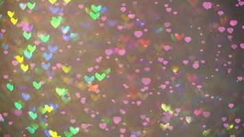 pequeños corazones cayendo al suelo y desenfocado corazón en forma de arco iris