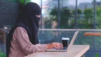mulher muçulmana com hijab de rosto inteiro trabalhando com um laptop video
