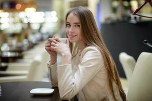 Beautiful smiling woman drinking coffee in cafe