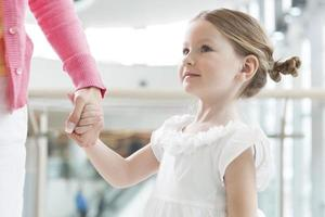 Young daughter holding mothers hand photo
