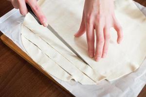 hands cutting store-bought dough photo