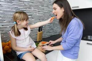 Young woman and little girl eating carrots in the kitchen