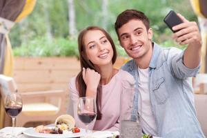 Attractive boyfriend and girlfriend are photographing themselves in cafe photo