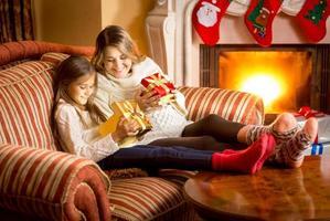 madre e hija mirando dentro de la caja de regalo de navidad