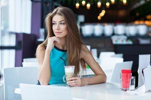 Portrait of a beauty young woman sitting in coffe shop photo
