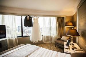 Bride and Groom Dress in Bedroom photo