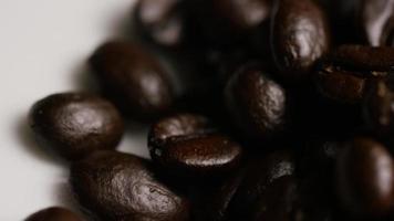 Foto giratoria de deliciosos granos de café tostados sobre una superficie blanca - granos de café 074