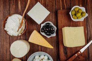 Vista superior de queso con aceitunas sobre fondo rústico