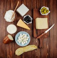 Top view of cheese on a wooden cutting board with a kitchen knife and pickled olives on a rustic background