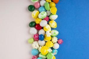 Vista superior de caramelos de colores sobre un fondo azul y blanco
