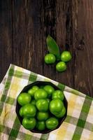 Ciruelas verdes ácidas en un recipiente sobre una servilleta a cuadros sobre un fondo de madera oscura.