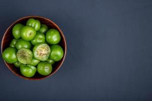 Ciruelas verdes en un recipiente de madera sobre un fondo negro foto