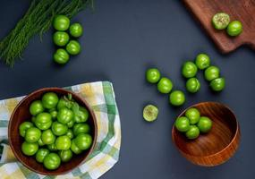 Top view of sour green plums in wooden bowls on a black background