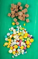 Vista superior de cubos de azúcar morena con varios caramelos de colores