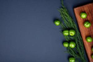 Vista superior de ciruelas verdes ácidas e hinojo sobre una tabla de cortar de madera sobre un fondo negro