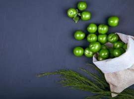 Top view of a sack of sour green plums on black background