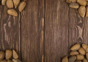 Top view of a wooden table with almonds and walnuts on it photo