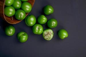 Ciruelas verdes ácidas esparcidas sobre un fondo negro foto