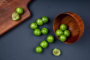 Vista superior de ciruelas verdes en un recipiente de madera con una tabla de cortar sobre un fondo negro