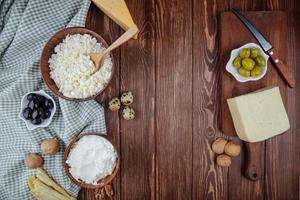 Top view of various cheeses with walnuts, quail eggs, and pickled olives on wooden background