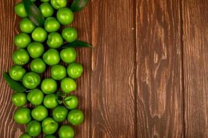Top view of sour green plums on a wooden background